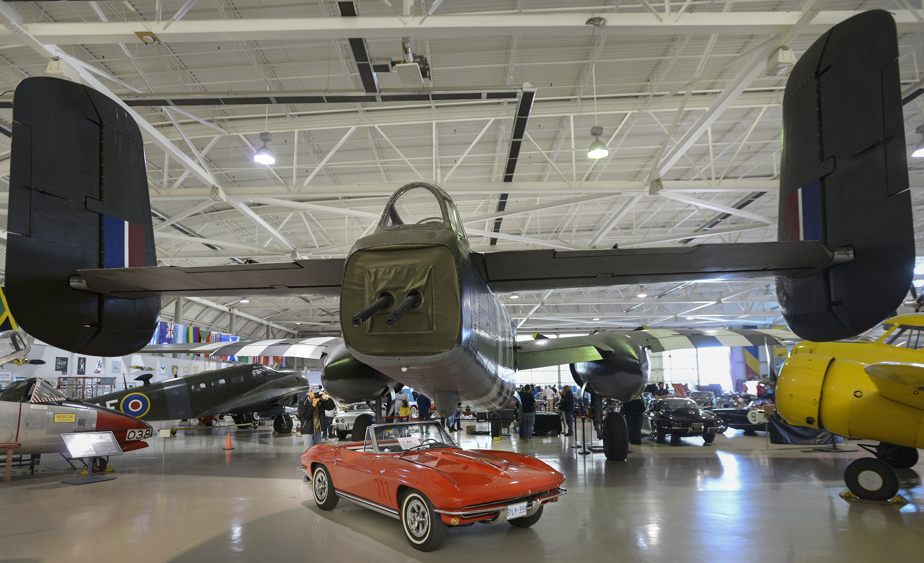 A Corvette owner photographs a 1965 Sportsman Corvette beneath the tail of a B2J Mitchell Bomber, one of 164 that flew with the RCAF between 1944-62, during the National Corvette Resorers Society 2016 Regional Judging Meet at the Canadian Warplane Heritage Museum Saturday.  The event is held in Canada every five years, the other four in the United States, and featured 66 Corvettes being judged on their originality and condition.  The Corvettes, some from as far away as West Virginia and Pennsylvania, had to be at least 15 years old to be entered.  John Rennison The Hamilton Spectator 9/24/16